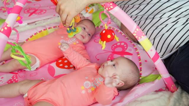 vídeos y material grabado en eventos de stock de padre jugando con twin baby girls en una alfombra de juego - padre que se queda en casa