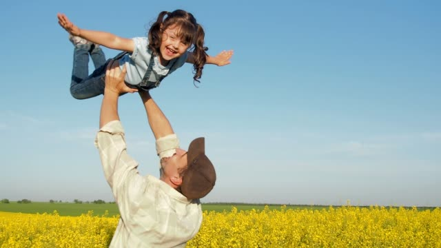 father plays with daughter in nature. - canola video stock e b–roll