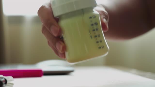 아버지는 그녀의 아기를 위해 양조 우유를 준비 - formula 1 스톡 비디오 및 b-롤 화면