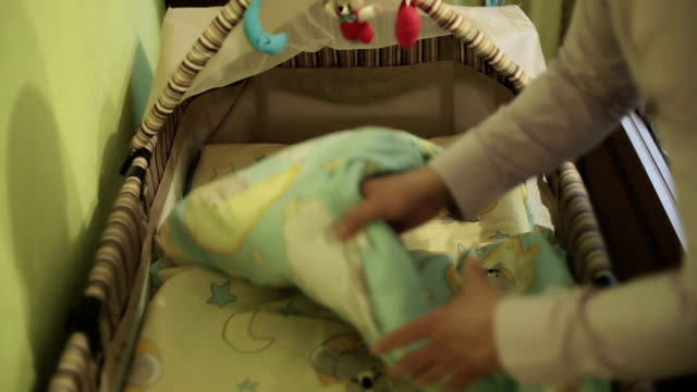 Father prepares bed for a newborn baby. video