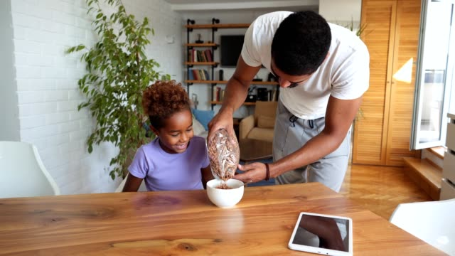 father preparing chocolate cereal for daughter's breakfast - padre single video stock e b–roll