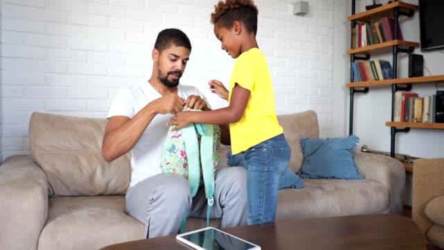 hazırlanıyor baba kız okul için - sırt çantası stok videoları ve detay görüntü çekimi