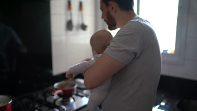 Father preparing lunch with his son on his lap