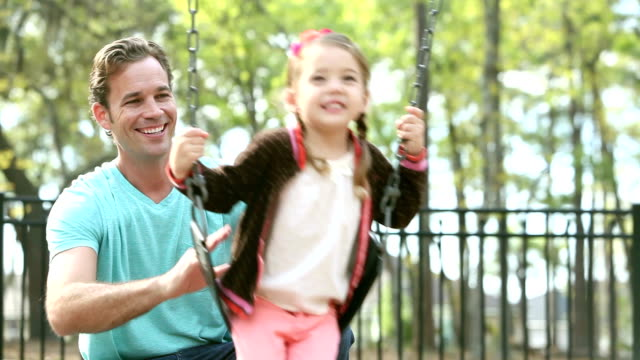 Father pushing daughter on swing in park video