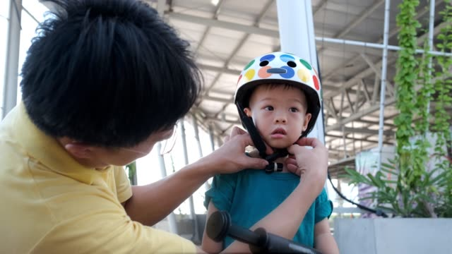father put helmet on  asian 2 year old toddler baby boy child - fathers day stock videos and b-roll footage