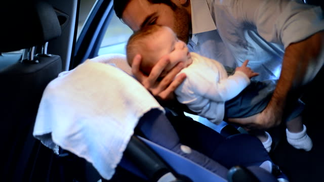 Father puts baby daughter in car seat, side view A father puts his 3 month-old baby daughter in a car seat and attaches the seat belts. Side view, seen from inside the car. seat stock videos & royalty-free footage