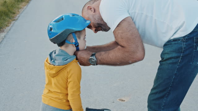 MS SLO MO Father putting crash helmet on sons head Father putting crash helmet on sons head before bike ride crash helmet stock videos & royalty-free footage