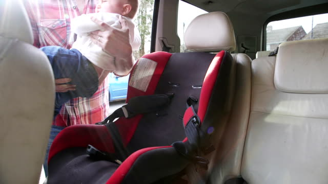 Father Putting Son In Safety Seat On Car Journey video