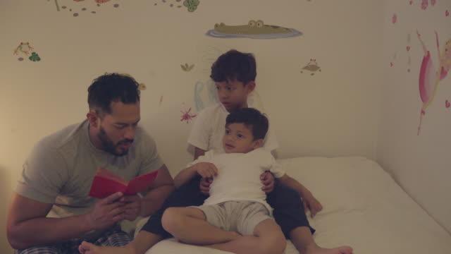 ein vater liest eine geschichte für seine kinder - lateinische schrift stock-videos und b-roll-filmmaterial