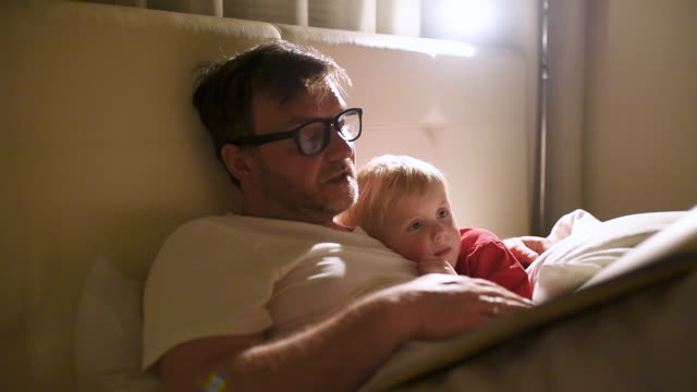 Father reading bedtime stories to child. Dad putting son to sleep.