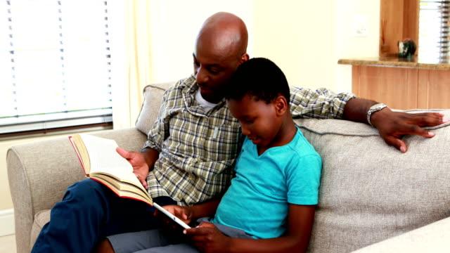 far läsa bok och son med digital tablett i vardagsrummet 4k - digital reading child bildbanksvideor och videomaterial från bakom kulisserna