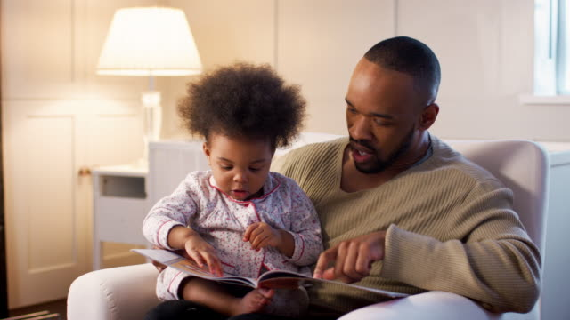 father reading book to young son at home in nursery - 2 3 anni video stock e b–roll