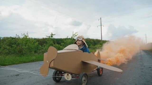 vídeos de stock e filmes b-roll de father rolls his son on a homemade cardboard plane - crianças todas diferentes