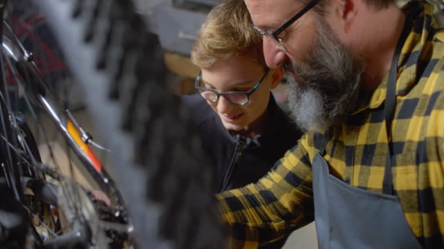SLO MO Father showing his son how to oil the bike chain