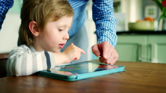 vídeos de stock e filmes b-roll de father showing son how to use digital tablet - hygge