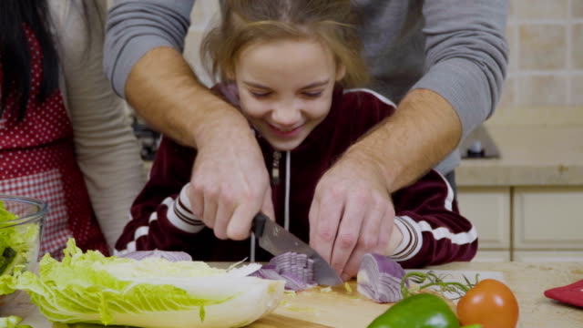 Father shows a little daughter how to cut onion Young housewife with husband stands near the table and preparing dinner for family. Their little daughters helps them to cook the salad. Father teaches a younger girl how to cut the onion. onion stock videos & royalty-free footage