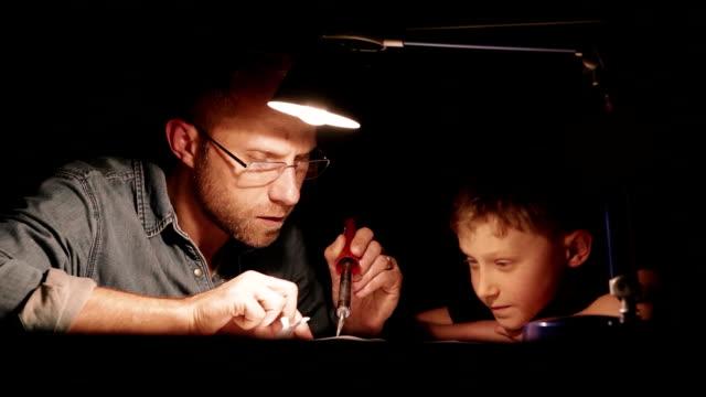 vídeos de stock, filmes e b-roll de pai sentado junto com o filho soldando enquanto consertando aparelho sob lâmpada de mesa brilhante - dia dos pais