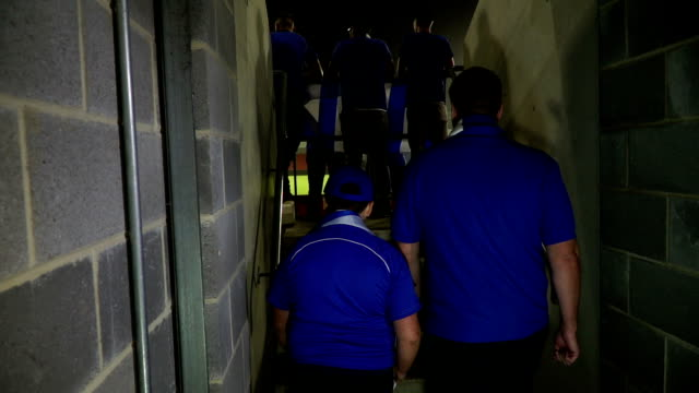 Father & Son Soccer / Football fans walking into Stadium Stock 4K video clip footage of a father and son football / soccer fans walking up the steps into the stadium as they go to cheer on their team. floodlit stock videos & royalty-free footage