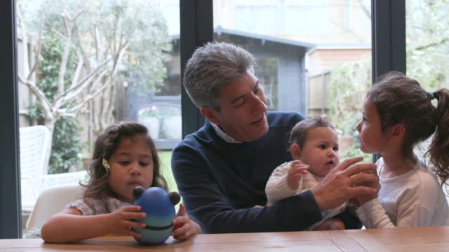 父親は若い家族と家で時間を過ごす - 兄弟姉妹点の映像素材/bロール