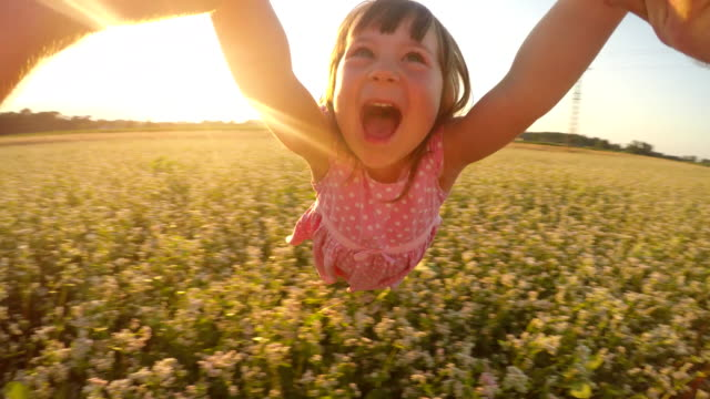 SLO MO POV Father spinning his cute daughter in field Slow motion POV shot of a father holding his daughter's hands and spinning her around in the middle of the buckwheat field. Also available in 4K resolution. angle stock videos & royalty-free footage