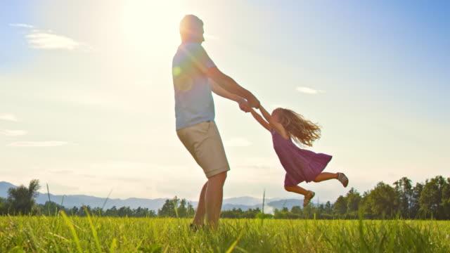 SLO MO 父と娘で楽しめる太陽が降り注ぐ草地 ビデオ