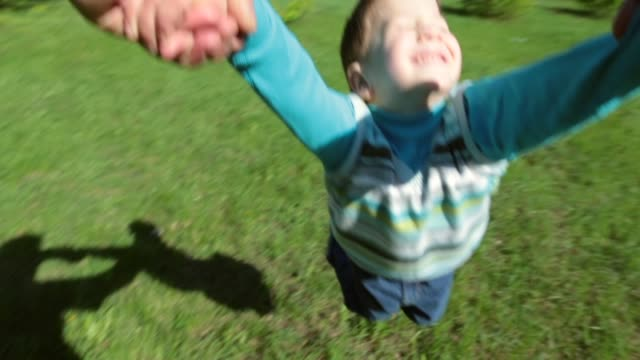Father spinning his happy son Father spinning his happy son on green lawn in park, slow motion, POV swinging stock videos & royalty-free footage