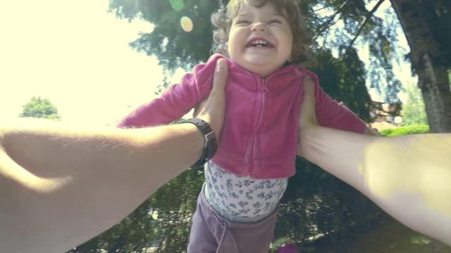 padre fiore figlia in giro sua le braccia - oscillare video stock e b–roll