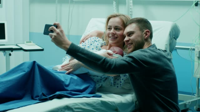 father takes selfie of him with his wife holding newborn baby while lying on the hospital bed. happy young and smiling family. - bambino appena nato video stock e b–roll