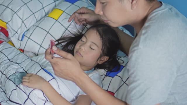 padre si prende cura della figlia malata,slow motion - china drug video stock e b–roll