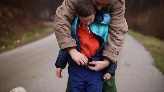 vídeos y material grabado en eventos de stock de padre teniendo cuidado de hijo - abrigo