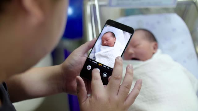 Father taking photo to his baby boy with smart phone