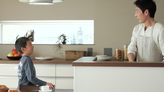 父と息子の話題のキッチン - 居間点の映像素材/bロール