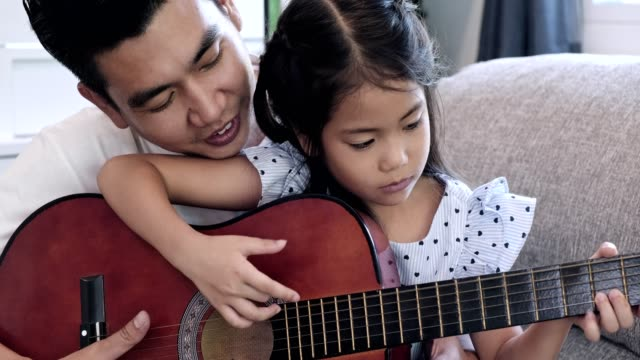father teach children guitar. asian man and child sitting together on sofa in living room learning to play guitar. close up shot. - музыкальный инструмент стоковые видео и кадры b-roll