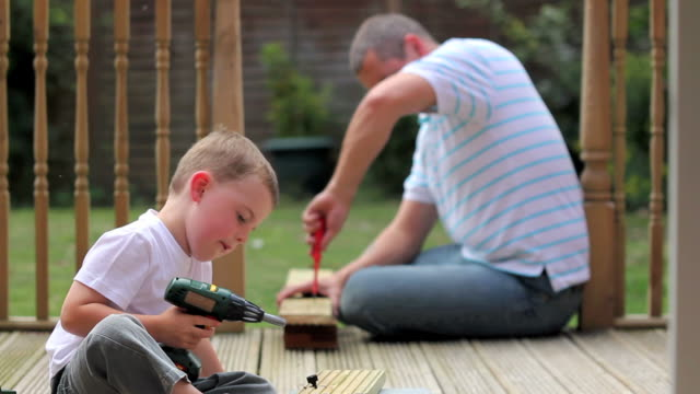 Father teaches son some home improvement skills video