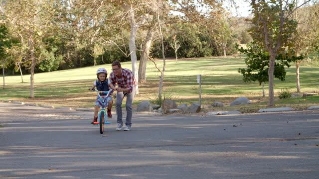 far undervisning dotter cykla på landsbygden väg - enbarnsfamilj bildbanksvideor och videomaterial från bakom kulisserna