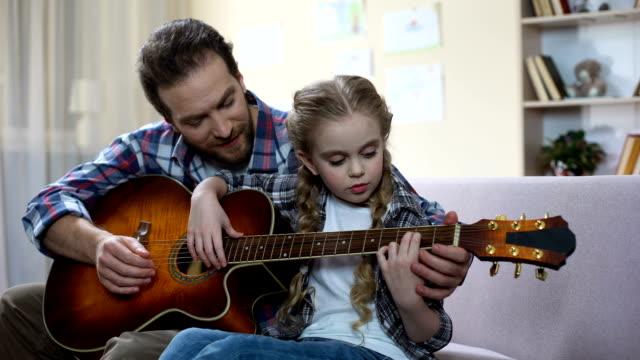 vídeos de stock, filmes e b-roll de filha de pai ensinar a tocar guitarra em casa, passatempo musical, lazer familiar - pai e filha