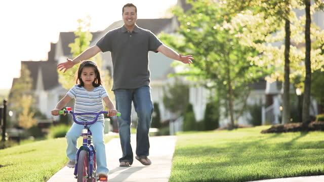 padre che insegna alla figlia a andare in bicicletta sul marciapiede del quartiere - padre single video stock e b–roll