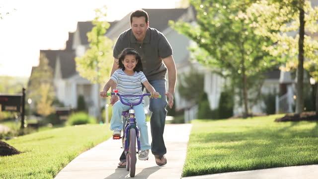 far lär dotter att cykla på trottoaren i grannskapet - enbarnsfamilj bildbanksvideor och videomaterial från bakom kulisserna