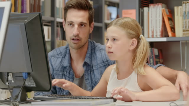 DS Father teaching his daughter browsing for books on a library computer video