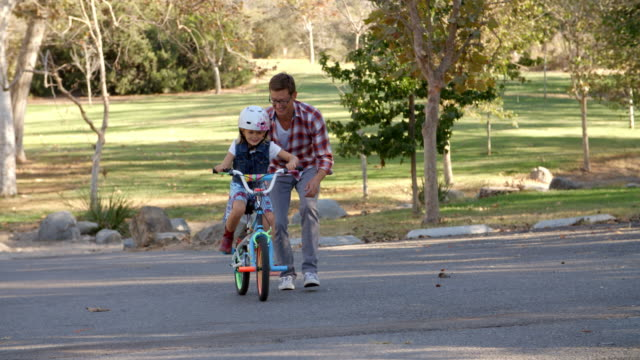 Father teaching his daughter to ride a bike in a park