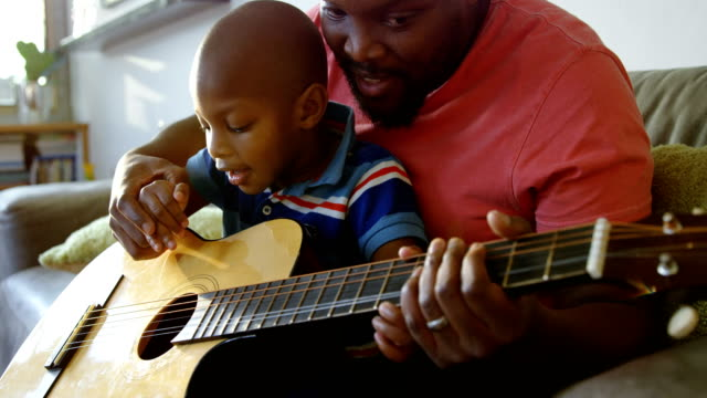 Father teaching his son how to play guitar at home 4k