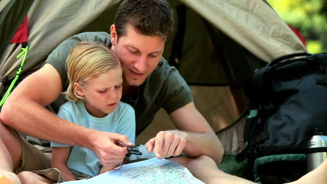 Father teaching his son to use a map video