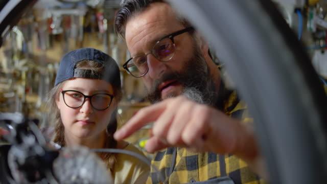 vidéos et rushes de slo mo père enseignant à sa fille adolescente comment servir la chaîne sur son vélo - père