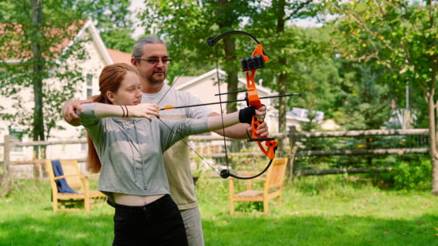 Father teaching his teenager daughter to shoot a bow video