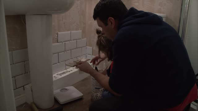 father teaching his young daughter how to tile and home improvement skills - porcelain stock videos & royalty-free footage