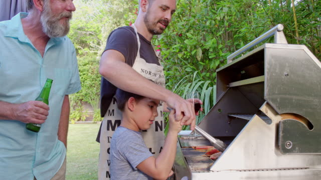 father teaching son how to cook in the barbecue - alla griglia video stock e b–roll