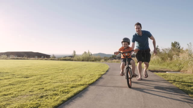 Father teaching son to ride a bike video