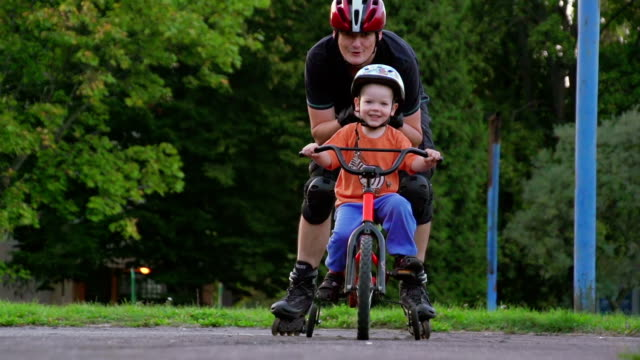 Father teaching son to ride bicycle video