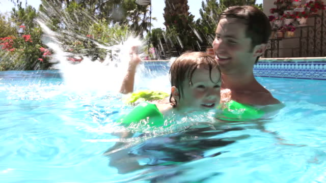 Father Teaching Son To Swim In Pool video f60e0e7b3