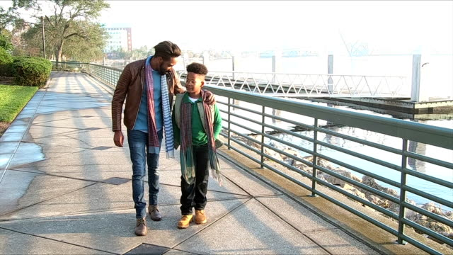 father, teenage son walking, talking on city waterfront - genitori video stock e b–roll